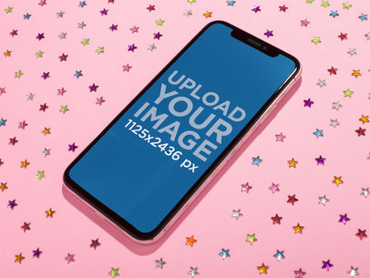 Jet Black iPhone X Mockup Lying on a Pink Surface with Bright Stars Stickers a19122