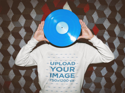 Woman Wearing a Crewneck Sweater Mockup while Holding a Blue Vinyl Against her Face a18835