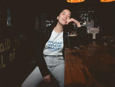 Asian Woman Drinking a Beer Wearing a T-Shirt Mockup at the Bar a18846
