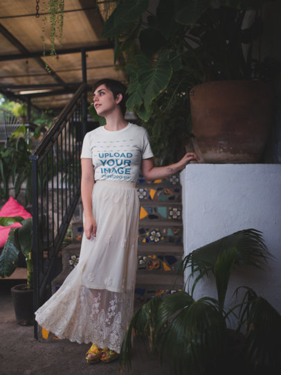 Artistic Portrait of a Woman Wearing a T-Shirt Mockup and a White Skirt Near Plants a18473