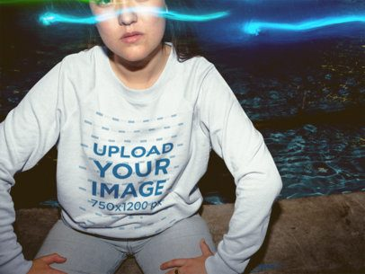Blue Lights on a Girl Wearing a Crewneck Sweater Mockup Sitting Down Near a Fountain a18858