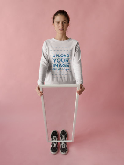 Beautiful Woman Wearing a Crewneck Sweatshirt Template in a Pink Room while Holding a Mirror a18510