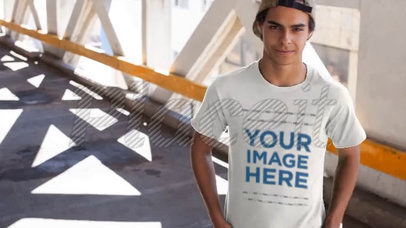 Young Dude Wearing a Snapback Hat and a T-Shirt Video Mockup on a Bridge a12867