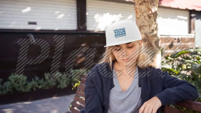 Young Girl Wearing a Snapback Hat Video Mockup While Sitting on a Bench Outdoors a14142