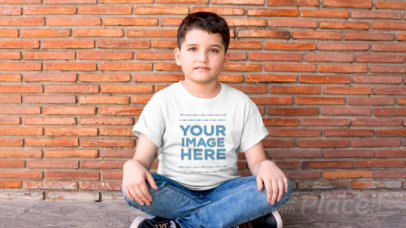 Boy Sitting with his Legs Crossed Wearing a T-Shirt Video Mockup a12772