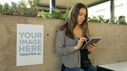 Young Business Woman Using An iPad With A Poster Video Mockup Besides Her a13888