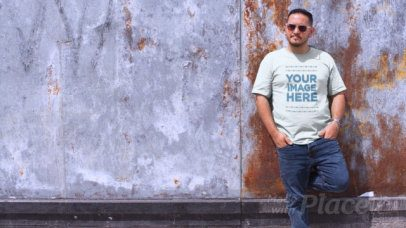 Video of a Man Wearing a Plus Size T-Shirt in a Sunny Day Against a Rusty Wall a12465