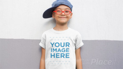 Kid Wearing a Hat and a T-Shirt Video Against a Two Tones Wall a12543