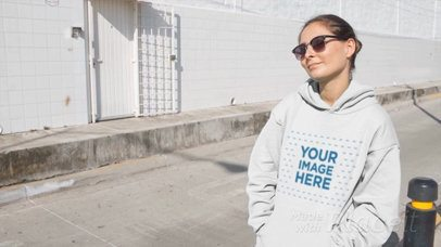 Woman Wearing a Hoodie Video and Sunglasses Sitting on Bumper Industrial Street a13095