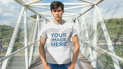 Young Trendy Guy Standing on a Bridge Wearing a Round Neck Tee Video Mockup a13012