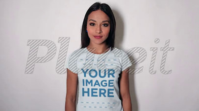 Smiling Pretty Girl Wearing a T-Shirt Stop Motion Video Leaning Against a White Wall a13160
