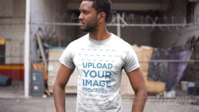 Handsome Black Man Wearing a Tshirt Video Standing Outside an Abandoned City Building a12119