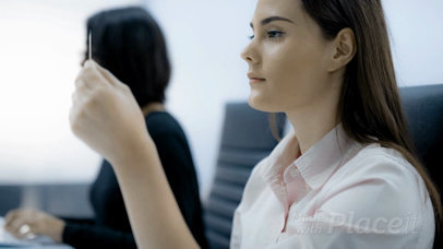 Office Girl Looking at a Business Card Video While at Work a13916