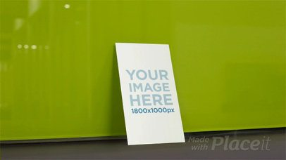 Business Card Falling in Stop Motion From Green Wall a13706