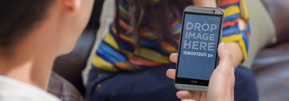 HTC One Mockup In Portrait Position Held by a Man on a Date Wide