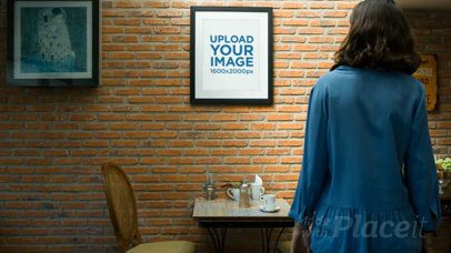 Girl at a Coffee Shop Looks at a Framed Art Print Video on a Bricks Wall a14356