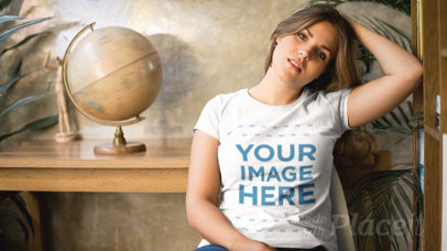 Girl Sitting on a Chair Wearing a T-Shirt Cinemagraph Near a Spinning World Globe a13481