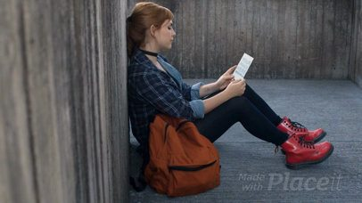 Pretty Redhaired Girl Sitting Down While Holding A Flyer Video Mockup a13896