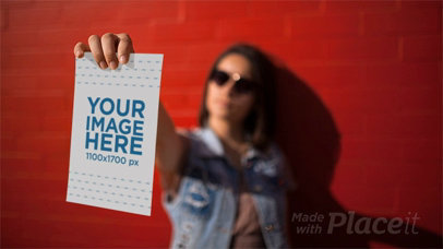 Woman Playing to be a Mannequin While Holding a Flyer in Stop Motion Near a Red Wall a13741