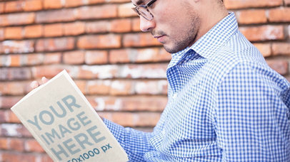 Mockup of a Cool Guy Wearing Glasses Reading a Book in Stop Motion While Sitting Down a13850