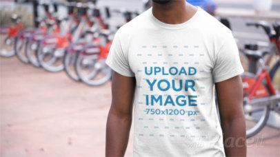 Young Black Man Wearing a T-Shirt Video Near a Bike Station in the City a12354