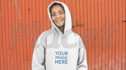 White Woman Wearing a Hoodie Video Standing Against a Red Metal Door a13097