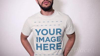 Trendy Guy With a Beard Wearing a T-Shirt and a Trucker Hat Against a White Wall a13473
