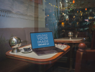Mockup of a MacBook Through the Window on a Restaurant Table with a Christmas Tree Behind It a19502