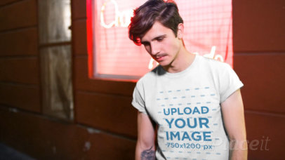 Hipster Man Wearing a Round Neck Tee Video Outside a Store at Night a13565