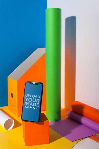 Portrait of an iPhone X Mockup Standing on a Colorful Desk a19722