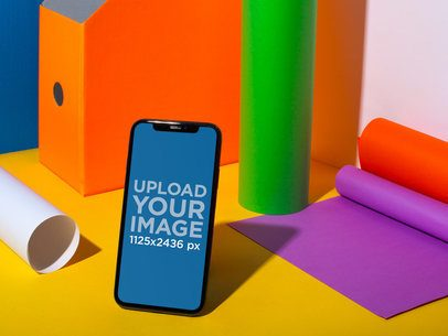 Black iPhone X Mockup on a Surface with Colorful Things a19723