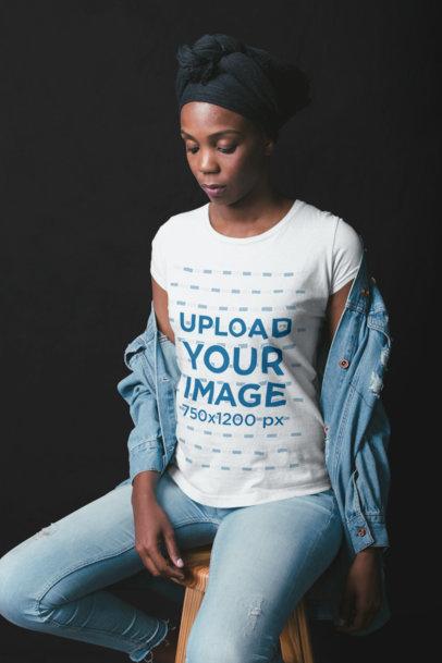 Black Woman Wearing a T-Shirt Mockup Sitting on a Stool at a Photo Studio a19765