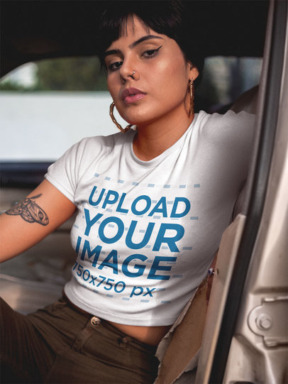 Woman Wearing a T-Shirt Mockup Sitting on a Car's Driver's Seat a19403