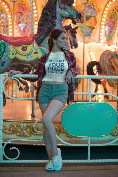 Pretty Woman Wearing a Crop Top T-Shirt Mockup Against a Carousel a19447