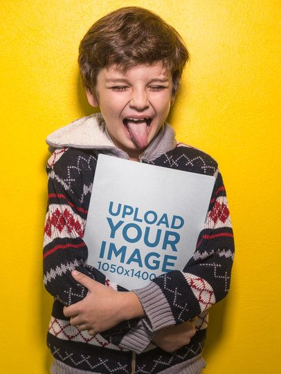 Boy Sticking His Tongue Out Holding a Book Mockup Against a Yellow Wall a19217
