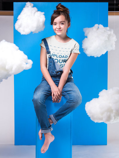 Mockup of a Girl Wearing a T-Shirt  Standing Against a Blue Cardboard with Clouds Hanging a19579