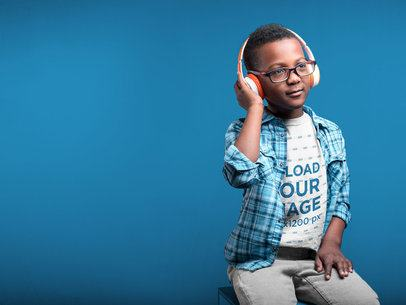 Black Kid Wearing a Tshirt Mockup Listening to Music in a Light Blue Room a19728