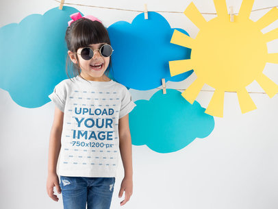 Smiling Girl Wearing a Round Neck Tshirt Template Near Cardboard Sun and Clouds a19480