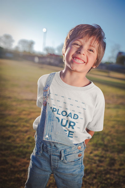 Smiling Kid Wearing a T-Shirt Mockup at a Park a20193