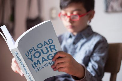 Closeup Shot Mockup of a Book Read by a Boy with Red Glasses a19158