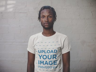 T-Shirt Mockup of a Man Against a White Brick Wall a20113