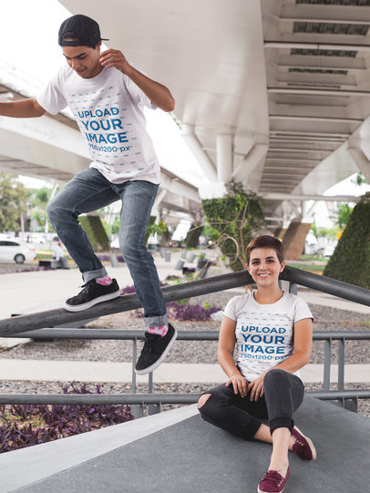 Boy and Girl Wearing T-Shirts Mockup While Jumping Under a Bridge a16434