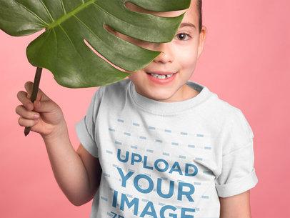 Girl Wearing a Tshirt Mockup Hiding Behind a Big Leaf a19909