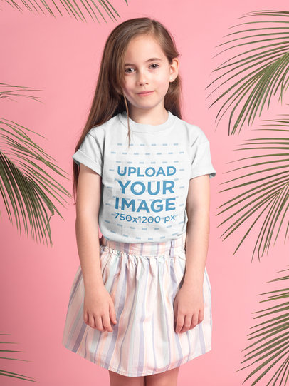 Little Blonde Girl Wearing a T-Shirt Mockup in a Pink Room with Green Leaves a19908