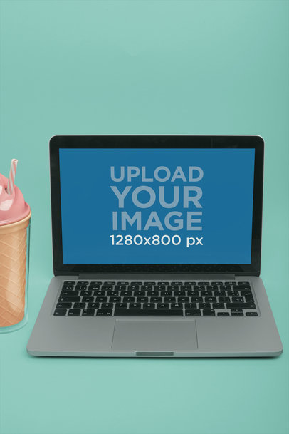 Portrait of a MacBook Mockup on a Solid Color Surface Near a Plastic Ice-Cream a20341