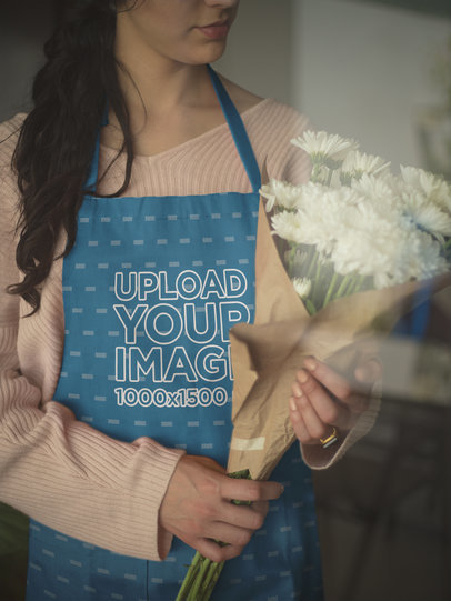 Closeup of an Apron Mockup Being Worn by a Girl Holding a Bouquet of White Flowers a19824