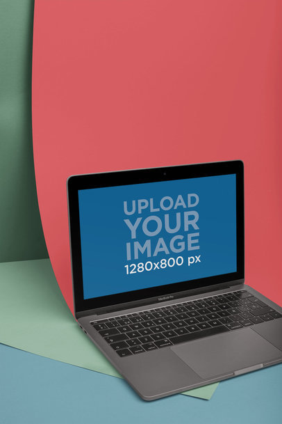 MacBook Mockup Lying in a Room Holding Two Colored Papers a20332