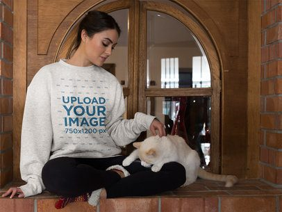Girl Wearing a Crewneck Sweater Mockup Petting her Cat Against a Window a18775