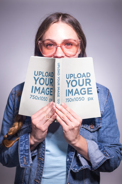 Woman with Glasses and Braids Holding an Open Book Mockup Against her Face a19256