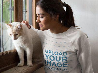 Closeup of a Beautiful Woman Wearing a Crewneck Sweatshirt Mockup Petting a White Cat Near a Window a18783